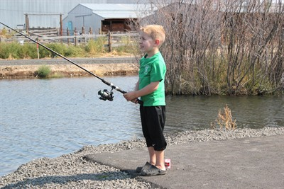 by: Photo by Holly M. Gill - Kaden Umnitz, 5, is all smiles as he tries his hand at fishing at the new Youth Fishing Pond.