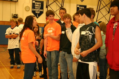 by: Photo by Susan Matheny - Link Crew members Yesenia Salgado, second from left, and Ryan Fine, help freshmen try to organize themselves by birth date without talking.