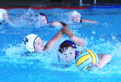 by: Photo By Joe McHaney - Elizabeth Armitage of the Madras girls water polo team pushes the ball through the water in a recent home match held at the Madras Aquatic Center.