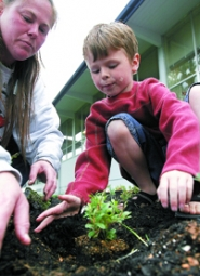 by: Jaime Valdez, Parent volunteer Jackie Kubat helps Raleigh Hills Elementary School kindergartner Cade Wolverton plant Kinnikinnick ground cover in the wildlife habitat garden.