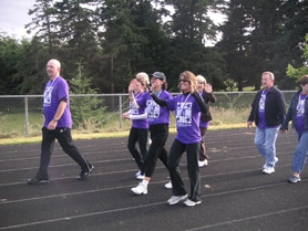 by: Nicole DeCosta, Sgt. Neil Hennelly, Mary Fieweger and Niki Johnston walk the first lap with other cancer survivors at West Linn's first Relay For Life event last week at the Rosemont Ridge track.