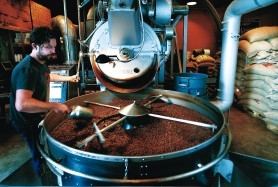 by: JIM CLARK, Stumptown roaster Joel Pollock cools a batch of coffee beans, which come from all over the world.