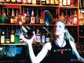 by: Christopher Onstott, American Cowgirls bartender Terri Leeseberg shows off her flair behind the bar.