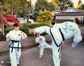 by: Elizabeth Ussher Groff, Emily Lee leads a Tae Kwon Do mini-class in front of the Woodstock Community Center on a beautiful early summer evening.  Pictured with her are student Avi Halpurin, age 7, and instructor Gary Wright.