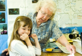 by: John Klicker, Grandma Robbie helps Sigal Tzafir, 7, with a writing project in first-grade teacher Carol Mack's Davis Elementary School classroom on Tuesday, June 27. Mack says she admires Robbie's versatility and her ability to identify with the children.