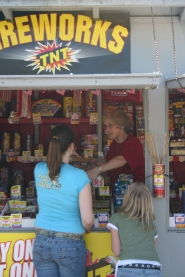 by: Garth Guibord, You can purchase legal fireworks from Sally Morrisson at this stand outside the Sandy Hi-School Pharmacy (or at many other places around town), or you can risk getting a hefty fine or even jail time by purchasing illegal fireworks.