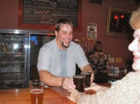 by: Contributed photo, Brewmaster Jeremy Carlson serves beers at last year's grand opening of the Karlsson Brewing pub in Sandy.