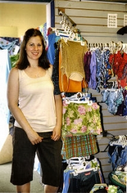 by: Rita A. Leonard, At the Swimsuit Warehouse, General Manager Amy Stell helps customers select affordable swimwear for the whole family