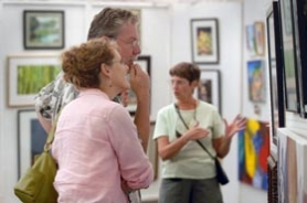 by: Vern Uyetake, Admiring paintings in the Open Show at the Festival of the Arts Friday are Sheila Martin and Rick Pittman.