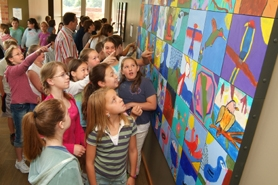 by: , Students who took part in the Youthful Art Healing Project admire the work of Middleton Elementary School.