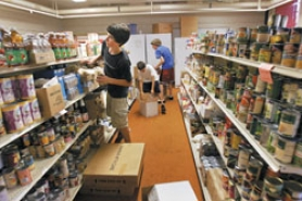 by: Jaime Valdez, FUTURE UNKNOWN — Evan Peick, 14 (left) Tyler Hanash, 12, and Spencer Mohalt, 14, stock the shelves at the Tualatin School House Food Pantry Tuesday afternoon. Even as the possibility of relocating looms in the near future, pantry volunteers are busy with trying to meet the community's demand for food.