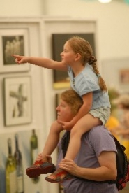 by: Vern Uyetake, Leslie Hoover and daughter Kira, 5, of West Linn, check out the art offerings last Friday at the Visual Arts Open Show in the Wells Fargo Pavillion Tent at the 43rd annual Lake Oswego Festival of the Arts.