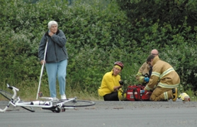 by: Clinton Vining, Estacada medics tend to a 46-year-old Boring man who received minor injuries when he collided on his bicycle with a car turning onto Highway 224.