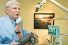 by: John Klicker, Gresham dentist Mike McKeel demonstrates the new technology that allows him to show patients their X-rays or photos of their teeth on this screen, which is attached to the patient's chair. McKeel was recently elected chairman of the ODS Companies, Oregon's largest dental insurer.