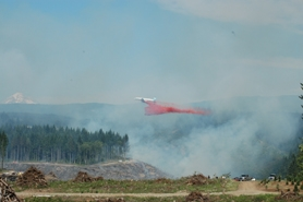 by: Clinton Vining, A tanker plane drops firefighting retardant on the Eagle Creek fire Sunday afternoon east of Estacada. The fire is believed to have been started by illegal fireworks.