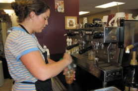 by: Barbara Adams, Sydney Drinkwater stirs a coffee drink at The Grind, a new coffee house located on Highway 224 next to the Estacada Clinic.
