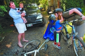 by: David Plechl, Sarah Gilbert kisses son Everett goodbye before riding her bike to a meeting. She and husband Jonathan Hanson (holding son Truman) will leave their SUV in the driveway during the family's month of public transit and pedal power.