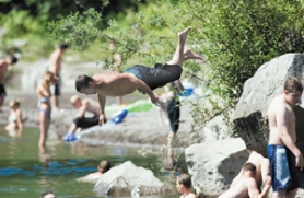 by: John Klicker, During the hot spell last week a youth jumps into the Sandy River, which can be dangerous because of the strong currents that can sweep objects downstream quickly.