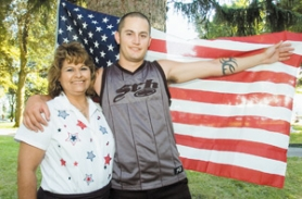 by: John Klicker, Marine Garrett Gould, 22, and his mother, Lorenia Rodriguez, pose with a flag he brought back from his six-month tour in Iraq. He is stationed at Camp Pendleton.