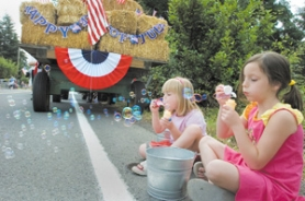 by: John Klicker, From left, Cora Bruders, 5, and her friend Carley Sprando blow bubbles along the Corbett parade route Tuesday, July 4.