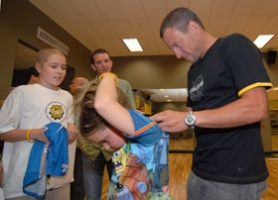 by: Vern Uyetake, Lance Armstrong signs a jersey worn by Jimmy Fowkes' 9-year-old sister, Molly. The family and Armstrong also had their photo taken together. Jimmy is a local brain cancer survivor