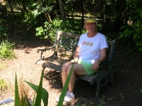 by: Cliff Newell, Paula Novak, president of the Rosemont-Summit Neighborhood Association, relaxes in the garden next to her home on Summit Street. Novak provided the leadership that led to the building of the garden, and she still works on it nearly every day.