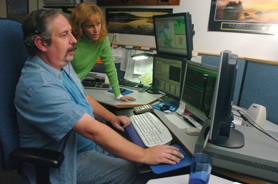 by: Vern Uyetake, Dispatchers John Wiggins and Leslie Taylor go above and beyond the call of duty while answering 9-1-1 calls for Lake Oswego Communications, which serves Lake Oswego, West Linn and Milwaukie.
