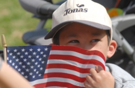 by: Vern Uyetake, Jonas Lamont peeks out from behind an American flag while enjoying the morning activities at George Rogers Park