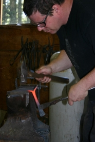 by: Garth Guibord, Blacksmith Andy Blakeney hammers a piece of heated iron into place during a workshop in an art cabin.