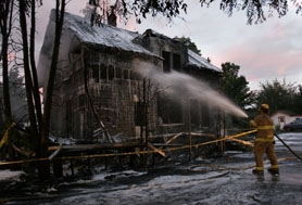 by: Jaime Valdez, Tualatin Valley Fire & Rescue firefighter Terry Taylor sprays foam on the Homestreet-Banyan Tree building on Southwest 185th Avenue in Aloha Sunday morning to prevent the blaze from starting again.