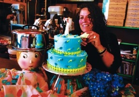 by: L.E. BASKOW, Piece of Cake owner Marilyn DeVault puts the finishing touches on a vegan wedding cake.