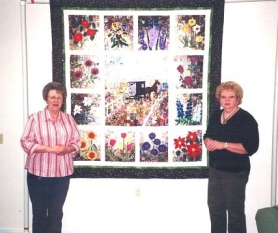by: Contributed photo, The Sandy Historical Society's 2006 Raffle Quilt is shown here with two of the five individuals who created the quilt, Pat Lee (left) and Shirley Crow. Not shown are Janet Bacon, Dianne Brines, and Vivian Bighaus. This quilt will be on display at the Historical Society's 8th Annual Quilt Show at Sandy High School July 14-16. Raffle tickets may be purchased at $1 each or 6 for $5. Profits go toward the completion of the new museum being built in Sandy.