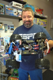 by: Barbara Adams, Mad Dogz Hobby owner Mike Hogue holds a Traxxas Revo racing car that will go up to 45 miles per hour, available at his new store on South Broadway in downtown Estacada.