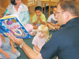 by: Brandy Slagle, Alexis Shadley and Abel Barrera, center, listen attentively to Troutdale Police Chief David Nelson as he reads to their class at the Mt. Hood Community College Head Start Center. The visit was part of a statewide campaign to raise awareness about the educational program.