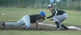 by: David Ball, Sandy first baseman Greg Luty tries to catch a runner too far from first base.