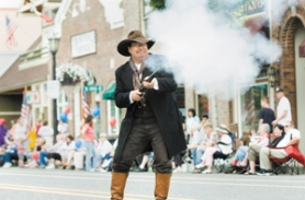 "by: John Klicker, Tom ""Turkey Creek"" Mannen fires a double-barreled shotgun at outlaws who robbed the bank and were getting away with the loot as the old west entertainers kicked off the Troutdale Parade with a shootout on Saturday, July 15, in downtown Troutdale."