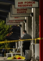 by: L.E. Baskow, A handgun rests on a sidewalk near the tarp-covered body of an unnamed man. Police say the man fired the gun at or near a police officer Wednesday in front of an armed forces recruiting center at the Eastport Plaza shopping center in Southeast Portland.