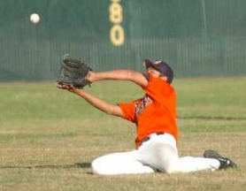 by: DAN BROOD, GREAT EFFORT — Suburban Door right fielder Levi Levesa makes a sliding catch of a fly ball in the Dawgs' game with Taylor Electric.