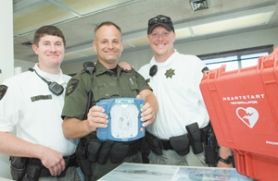 by: John Klicker, From left Steve Dangler, Lt. Michael Shults and Rian Hakala stand with an automated defibrillator. The two river patrol deputies were with Shults during a training session two months ago when he had a devastating heart attack. The defibrillator at the training site in Warrenton saved his life.