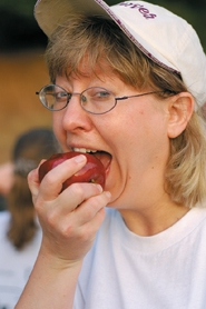 by: Barbara Adams, Susan Wagner, owner of Curves, takes a bite out of cancer during the Estacada Relay for Life Friday.