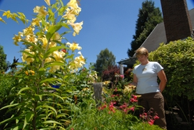 "by: Vern Uyetake, Above: Bonnie Jochim of West Linn stands amid a ranibow of color from her garden. Thirteen years ago Jochim and her husband, Lonny, began planting in separate areas of the yard and today the garden boasts several different ""rooms"" — areas for different activities. This weekend, this yard along with five others on River Street in West Linn will be on display with proceeds benefitting the neighborhing McLean House's upkeep."