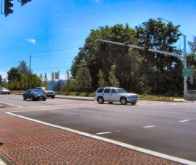 by: Eric Norberg, Looking diagonally across S.E. McLoughlin, at the junction of S.E. 17th and Harrison. The new patterned crosswalk design is in the foreground; a gas station which formerly occupied the lot out of the photo at left is gone, and so are the business buildings in the center distance which blocked views of the Willamette River from parts of downtown Milwaukie.