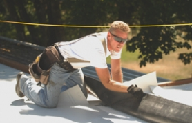 by: Vern Uyetake, Dan Dyke of Snyder Roofing rolls out roofing material on top of the Lake Oswego School District Administration building on Monday.  Dyke and four other employees re-roofed the building during the recent heat wave.