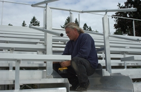 by: Ray Pitz, Everett Humphrey of SAL Development puts finishing touches on visiting spectator bleachers at Sherwood High School's athletic field the first week of July. The new seating will accommodate more than 550 people.