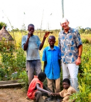 "by: Lisa Revell, David Stone with village farm boys, and neighbor Kolobil--who is holding his homemade flute, called a ""naam-pock"""