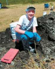 by: Barbara Sherman, IN HIS ELEMENT — MacKenzie Smith, wearing all the proper gear — boots, long pants, gloves, hairnet and hat — to protect a Woodburn archeological site, takes a break from the hot sun last week.