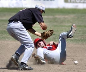 by: Jim Craven, Centennial's Troy Harris is tagged out by North Medford's Zack Earle despite a collision at second base during the first game of Tuesday's championship series.