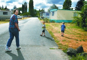 by: Jaime Valdez, Lisa Sollman walks down her street at Beaverton Mobilodge Wednesday, accompanied by her two children, Jacob, center, 6, and Isaac, 4. Residents at the park, along with tenants at the adjacent Nut Tree Estates and Young's Mobile Estates, have until Aug. 4, 2007, to move out.
