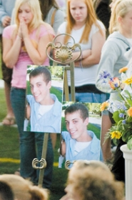 by: John Klicker, Friends of Kyle Riedel stand behind portraits of him at a candlelight vigil at Gresham High School's football stadium Thursday, Aug. 10. Riedel, who would have been a sophomore at the high school this fall, drowned Wednesday, Aug. 9, in the Deschutes River.