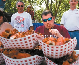 by: Jaime Valdez, CRAWFISH-CHOMPING CHAMP — Mike Rossi, of Portland, slurps up a crawfish tail during Saturday's adult crawfish-eating competition at the Tualatin Crawfish Festival. Rossi took home first place after eating 97 crawfish tails and claws.
